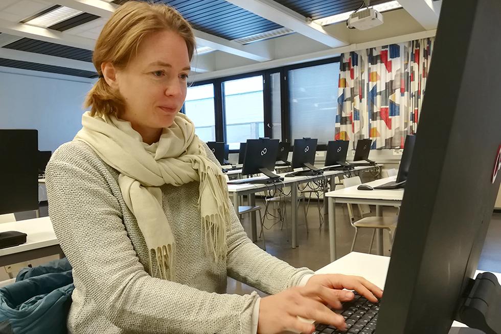 Nainen työskentelee tietokoneella tilassa, jossa paljon muitakin työskentelypisteitä.
